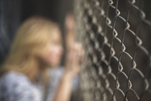a woman looking through a chain link fence