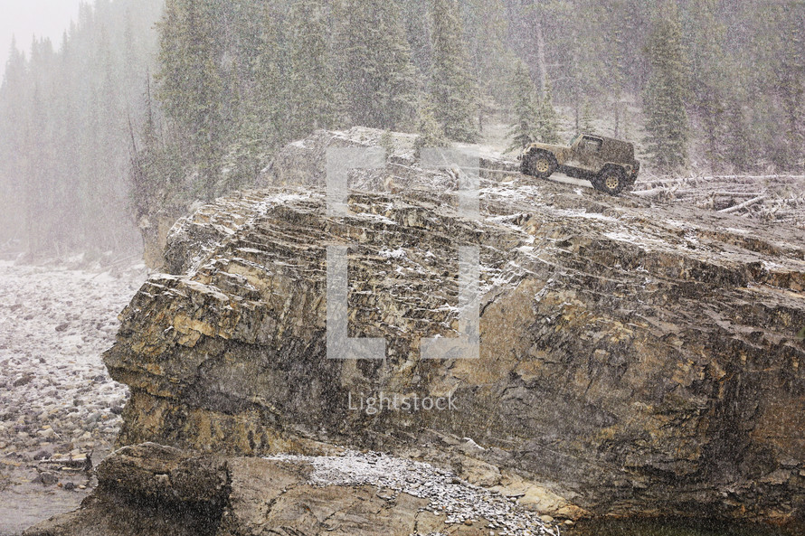 4 x 4 perched on a rocky cliff in a snowstorm