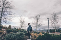 a man standing on campus under an overcast sky