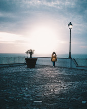 a woman in a coat looking over a railing out at the water