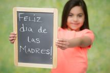 girl holding a Feliz dis de Las Madres sign