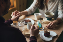 couple holding hands and drinking coffee with cupcakes