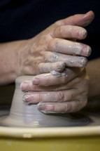 shaping clay on a potter's wheel