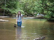 a teen girl with a net walking in a stream