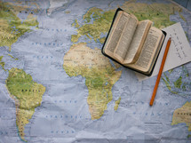 a Bible, notepad, and pencil on a map