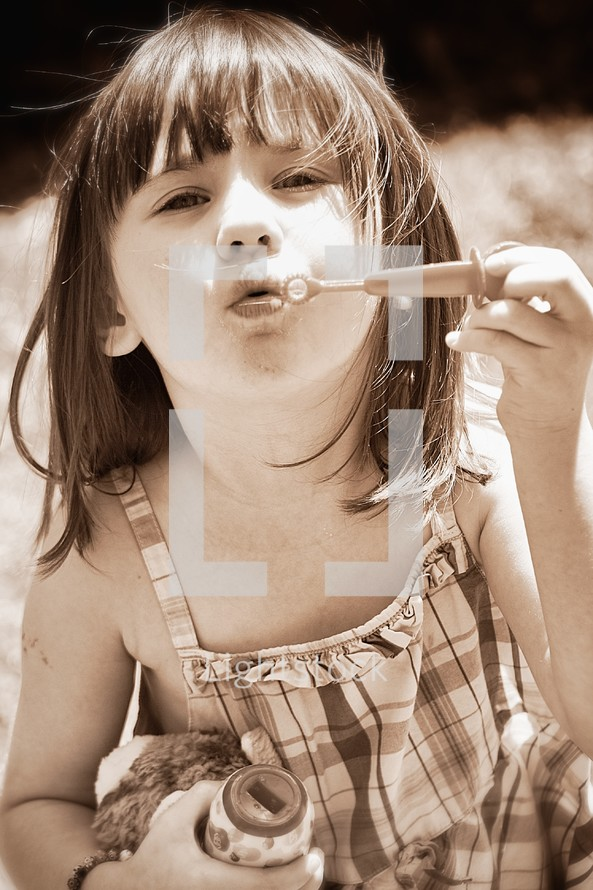 Girl holding stuffed anmial while blowing bubbles outdoors.