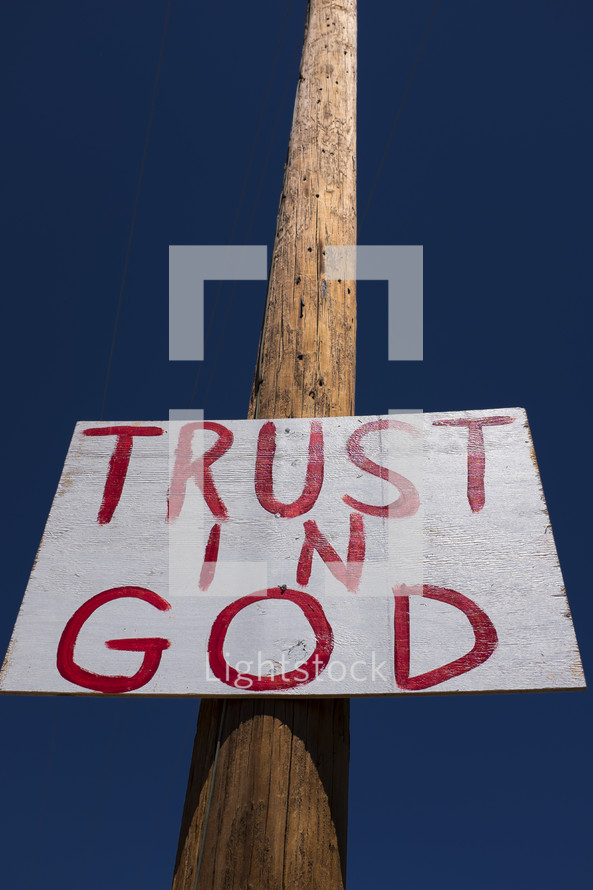 """""""Trust in God"""" sign nailed to a telephone pole."""