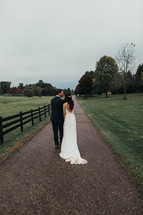 bride and groom and country road and fence line