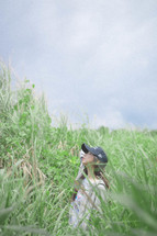 a woman standing in a field of tall grasses