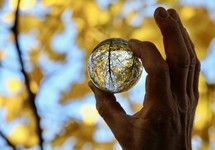 person holding a glass orb looking at fall trees