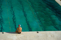 swimmer sitting at the edge of a pool