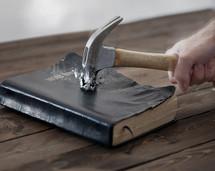 A hammer hitting a Bible.