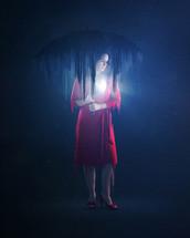a woman standing under an umbrella in darkness