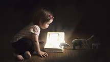 A toddler girl reading a Bible and learning about Noah's Ark