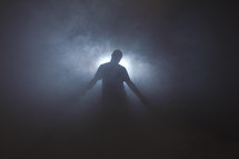man standing in front of glowing light