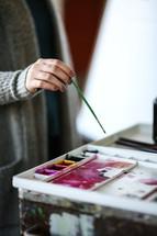 an artist holding a paint brush