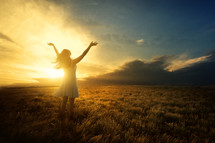 a woman with arms raised to God standing under the glow of sunlight