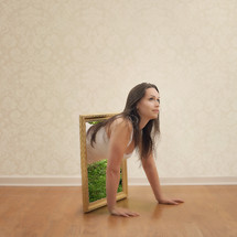 woman crawling out of a framed mirror
