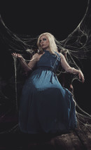 woman in a blue dress sitting in spider webs