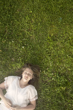 Teen girl with eyes closed laying a field of green grass.