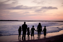 A family of six standing on a beach silhouetted against the sunset
