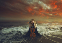 a woman with a viola kneeling in prayer in the ocean