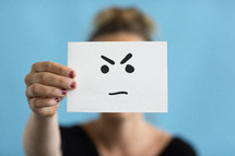 a woman holding up an angry face