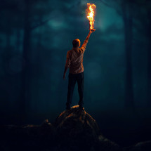 man holding up a flaming hourglass