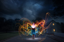 swirling colorful lights surrounding a woman at night