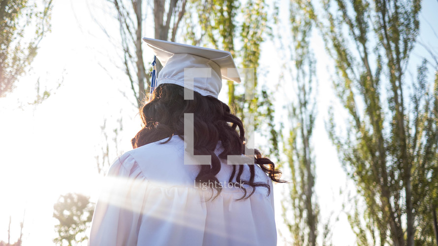 a graduate with her back to the camera