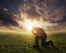 a man kneeling in prayer under the glow of the sun
