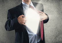 man in a business suit pulling open his shirt and revealing light