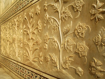detailed carved flowers along a wall of the Taj mahal