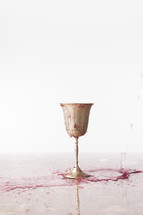 red wine spilling over a chalice onto a table