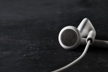 White ear buds crossing over on black table.