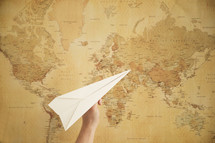 person flying a paper airplane in front of a world map.