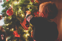 a toddler boy decorating a Christmas tree