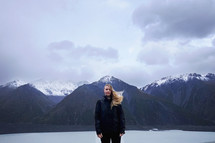 a woman standing in front of snow capped mountains with hair blowing in the wind