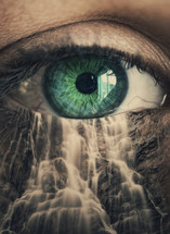 close up of an eye with a mountain waterfall super-imposed under the eye