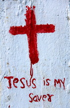 Roughly painted Christian Cross and the wording Jesus is my Savior in red paint on white background