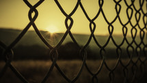 sunburst through a chain linked fence