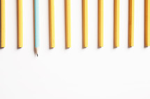 row of unsharpened pencils with one blue pencil sharpened.
