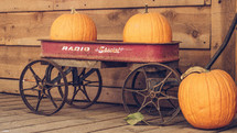 orange pumpkins in a red wagon
