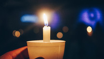 holding a candle at a candlelight service