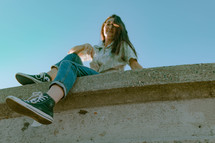 teen girl sitting on a concrete wall