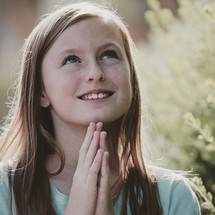A girl child with praying hands looking up to God and asking him to answer her prayers