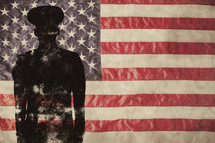Silhouette of a solder standing in front of an American flag.
