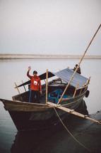 A man waving on a fishing boat