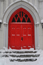 Red church doors stand out in the snow.