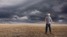 farmer holding a rake and looking up at storm clouds